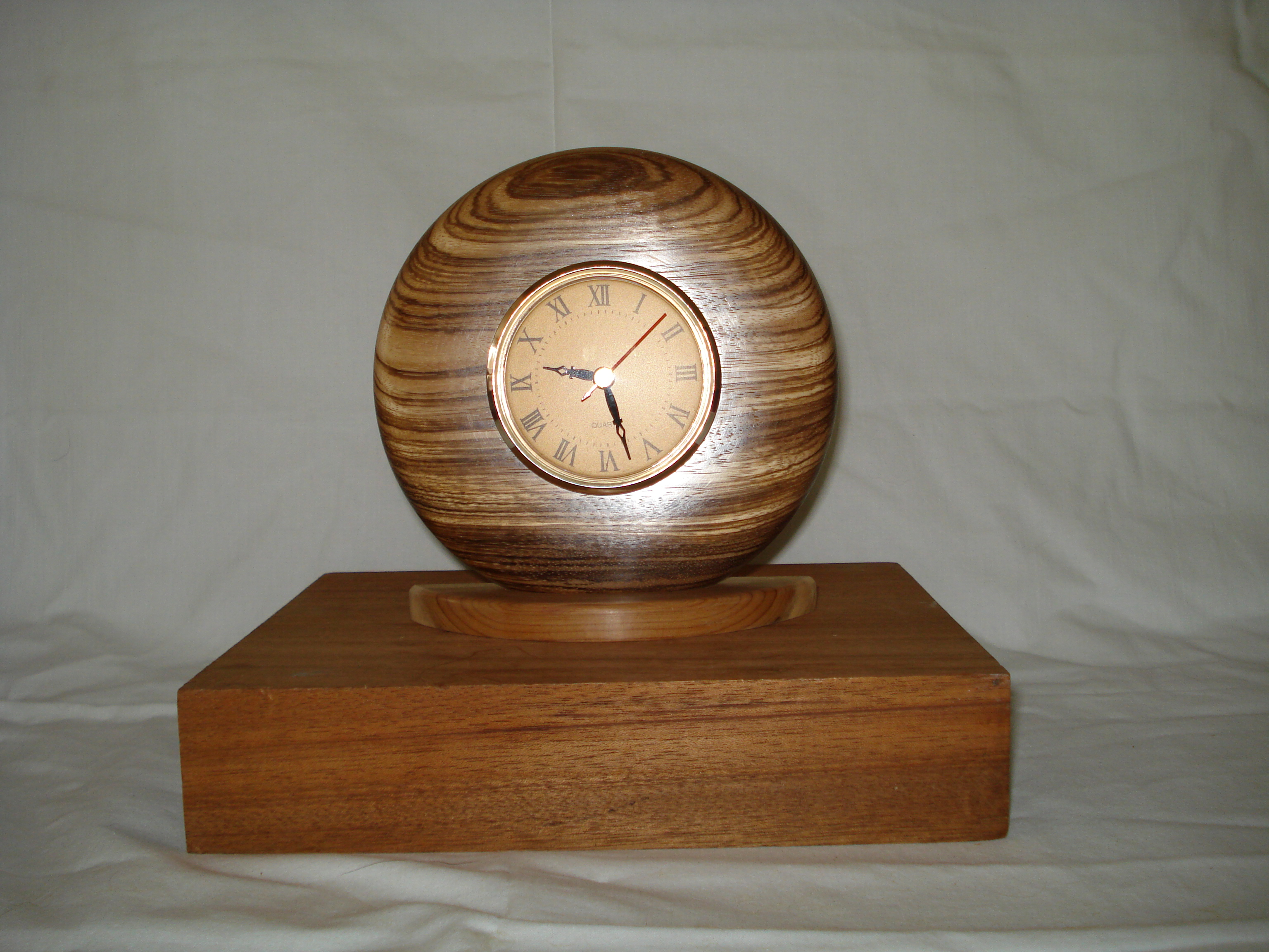 clock face in a Zebranno surround on a Yew base