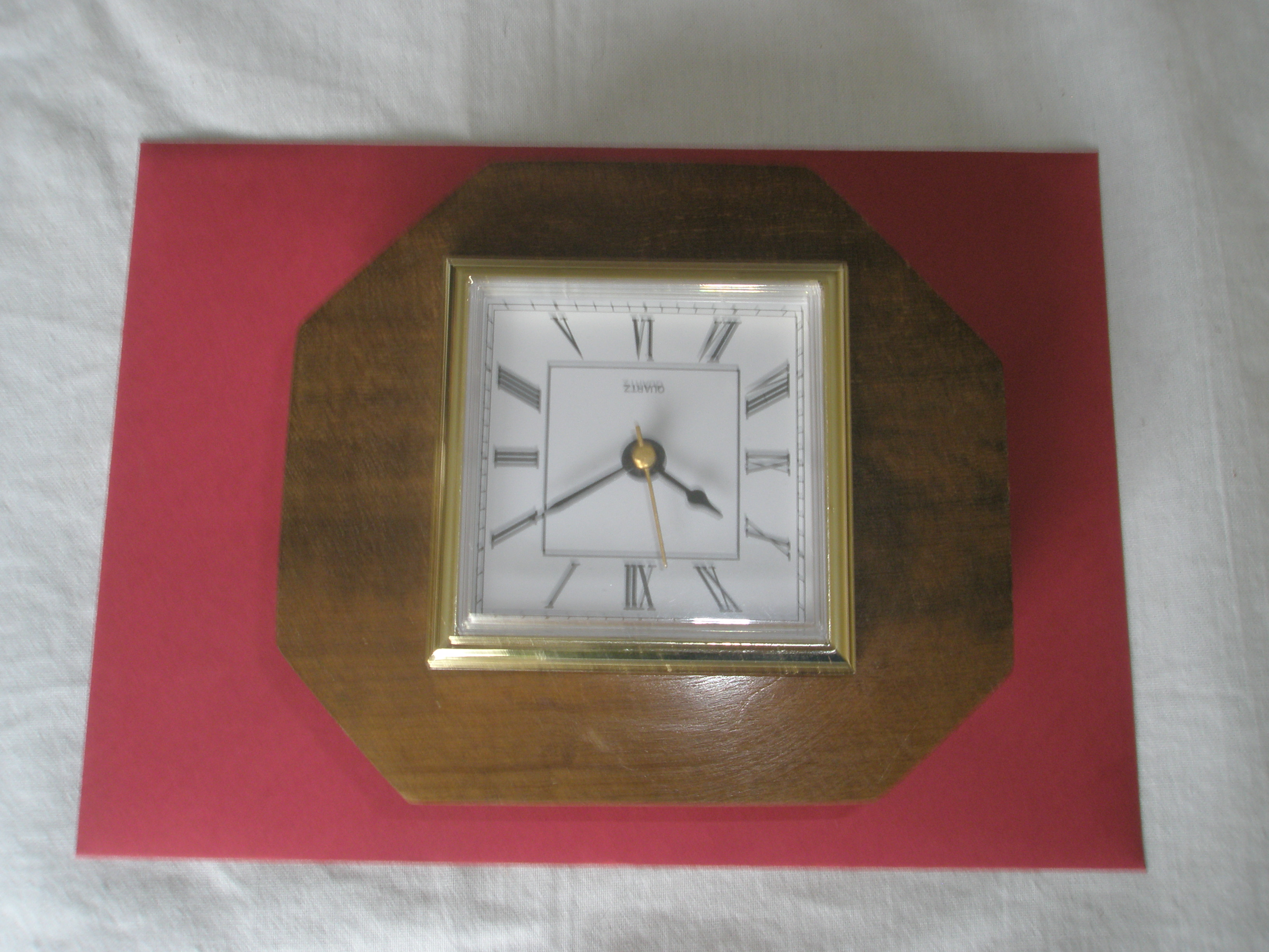 A table top Square white face clock with black numerals inserted on a round Mahogany base